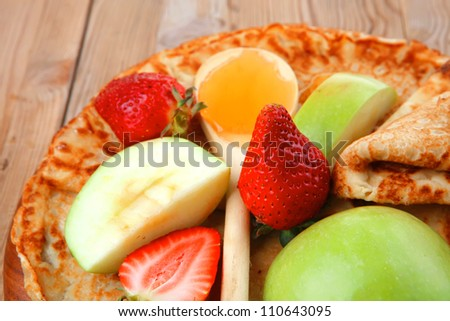 baked food : pancake with honey strawberries and apple on wooden table