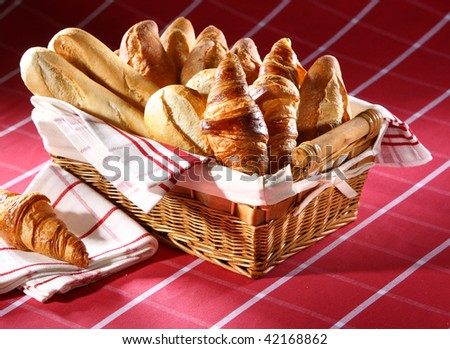 Baked goods in the basket on red tablecloth - stock photo