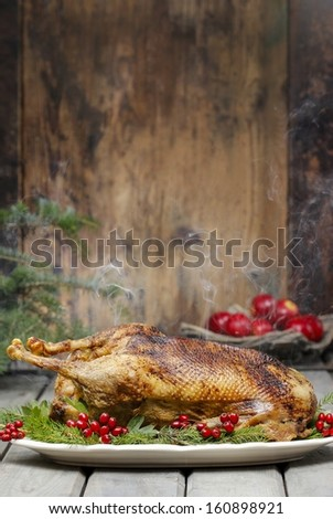 Baked goose on wooden table. Popular christmas dish - stock photo