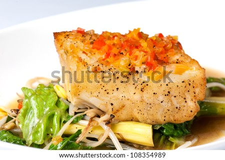 Baked halibut with vegetable garnish on a white plate - stock photo