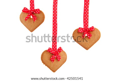Baked hanging gingerbread hearts with red speckles bows and ribbon