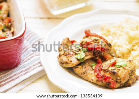 Baked honey mustard chicken thighs with roasted red bell peppers, toasted almonds and parsley - stock photo