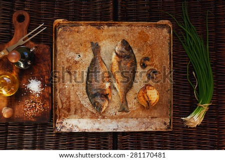 baked in the oven until golden brown fish gilt-head bream lying on vintage iron plate for oven,  - stock photo