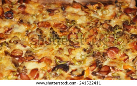 Baked Italian pizza with mushrooms, meat and melted cheese - stock photo