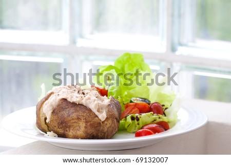 Baked jacket potato with tuna and fresh salad - stock photo