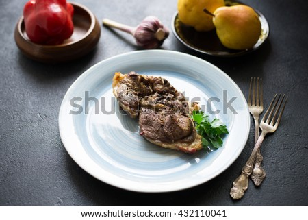Baked  lamb meat with pepper on a blue plate over dark background - stock photo