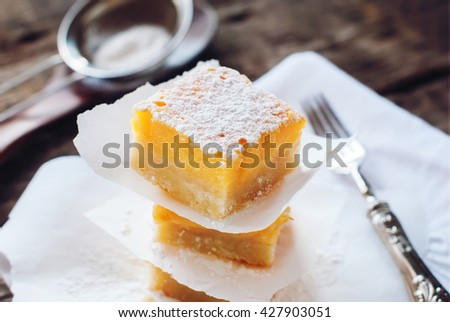 Baked Lemon Bars with Powdered Sugar Peaces in Stack Wooden Table
