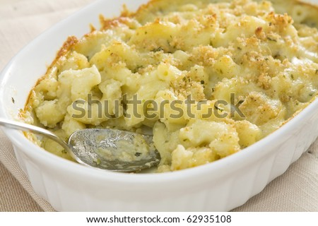 Baked macaroni and cheese made with pesto sauce, provolone cheese, and mozzarella cheese, then topped with bread crumbs.