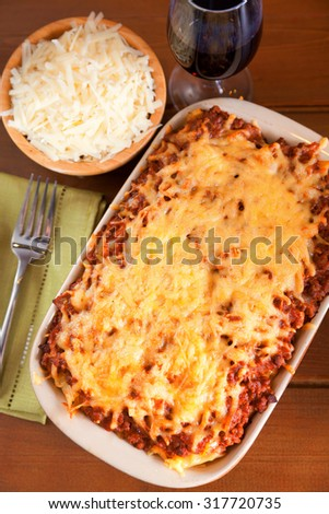 Baked Macaroni Bolognese with cheese and red wine next to the baking dish.