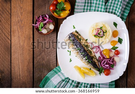 Baked mackerel with herbs and garnished with mashed potatoes and pickled vegetables. Top view - stock photo