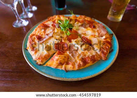 Baked meat pizza served on a blue plate on a brown restaurant table