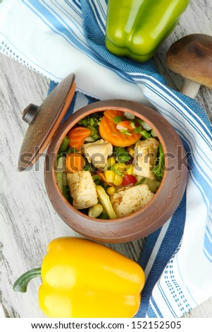 Baked mixed vegetable with chicken breast in pot, on wooden background - stock photo