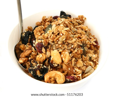 Baked muesli in white bowl with fruit and nuts on white background with a spoon - stock photo