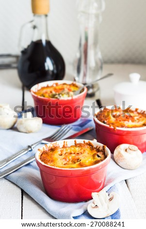 Baked mushroom julienne potatoes and tomato with cheese, lunch on a wooden background