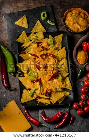 Baked Nachos with cheese dip and chili peppers - stock photo