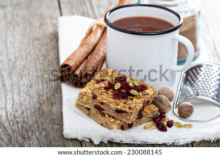 Baked oatmeal squares with cranberry and pumpkin seeds with spicy hot cocoa - stock photo