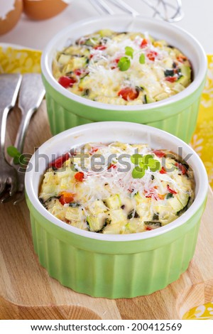 Baked omelet with vegetables and cheese in ramekins