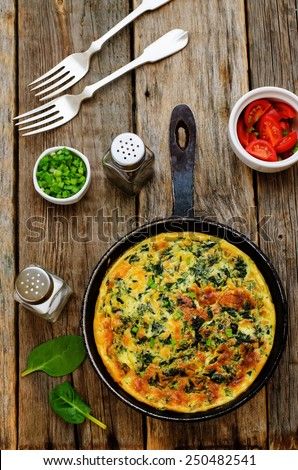 baked omelette with spinach, dill, parsley and green onions on a dark wood background. tinting. selective focus - stock photo
