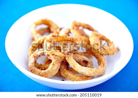 Baked onion rings - healthy variation of famous fast food recipe. - stock photo