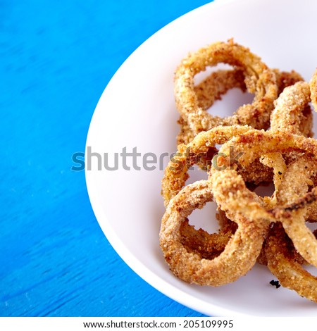 Baked onion rings snacks in white plate on blue background. Healthy fast food recipe. - stock photo