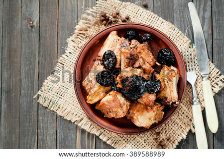 Baked or fried meat , pork ribs with prunes , spices and pepper on a dark wooden background - stock photo