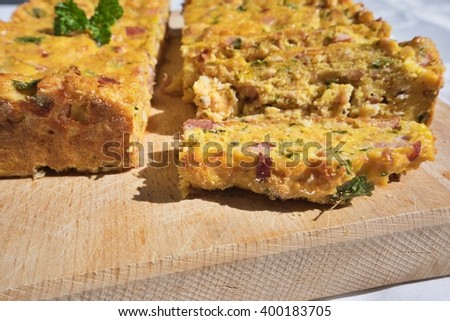 Baked or roasted egg pie kind of quiche or omelet, french style snack served on the chopping board. Made from eggs, smoked ham, parsley, pork meat and bread. Traditional spring food in Czech Republic. - stock photo