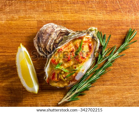 Baked oyster shell with cheese,  served with greens and lemon on a wooden background.  - stock photo