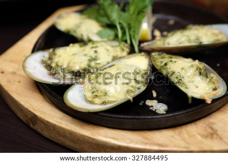Baked oysters on a plate in the restaurant - stock photo