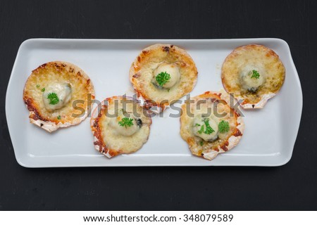 Baked parmesan scallops on black background, top view - stock photo