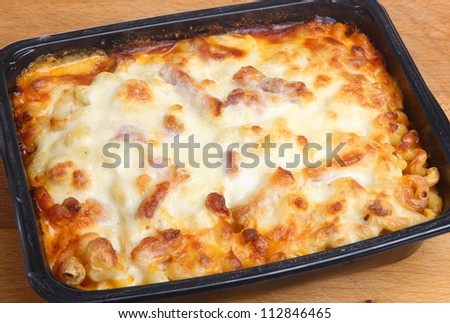 Baked pasta ready meal with spiral pasta, chicken, bacon and cheese. Family size pack. - stock photo