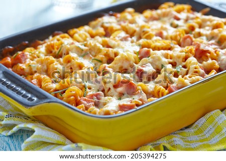 Baked pasta with ham and cheesy tomato sauce - stock photo