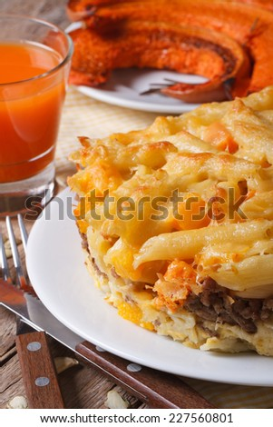 Baked Pasta with meat, cheese and pumpkin on a plate and vegetable juice. vertical