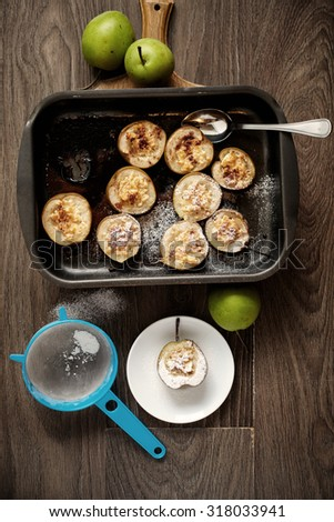 Baked pear with honey and chees, and cinamon on sheet, on the wooden table - stock photo