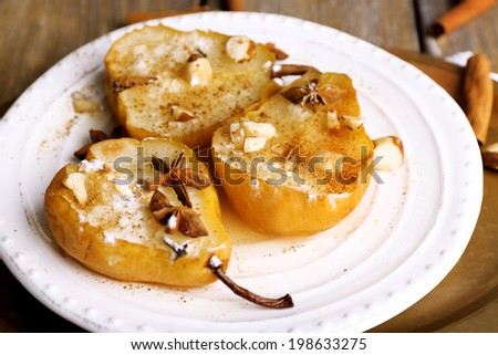 Baked pears with syrup on plate, on tray, on color wooden background