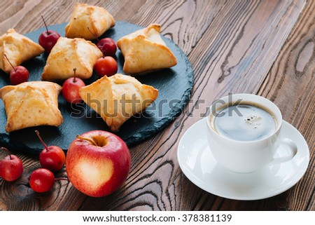 baked pies with apples on a black tray from slate, coffee in a white porcelain cup on a white saucer, paradise apples and red ripe apple with love heart on wooden table. - stock photo