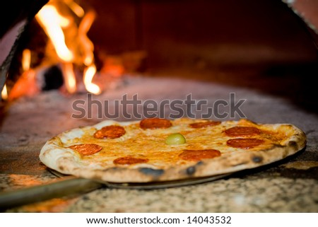Baked pizza by the fire in pizza oven - stock photo