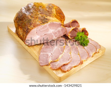 Baked pork neck on cutting board - stock photo