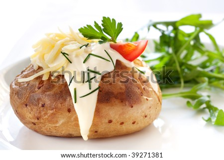 Baked potato filled with sour cream and grated cheese, with arugula on the side. - stock photo