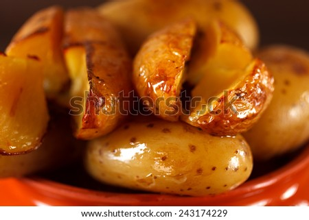 Baked potato in a clay pot on a background of the dark wooden surface. - stock photo