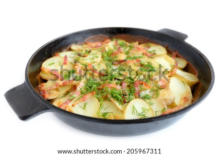 Baked potato in the cast iron skillet with bacon and dill isolated on white