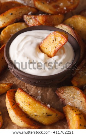 Baked potato wedges and mayonnaise macro on the table. Vertical
