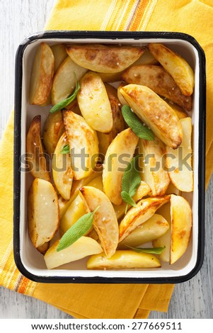 baked potato wedges in enamel baking dish - stock photo