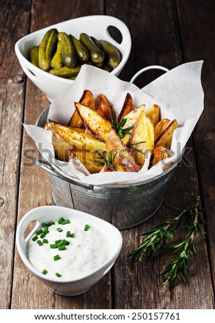 Baked potato wedges served with sauce and pickles - stock photo