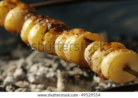 Baked potato with fat on skewer over coals - stock photo