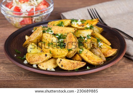 Baked potato with herbs and spices. Potato dish on the table. Baked potato and salad on the table with a napkin and fork. Hearty vegetarian lunch - stock photo