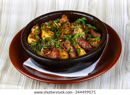 Baked potato with pork meat served fresh herbs - stock photo