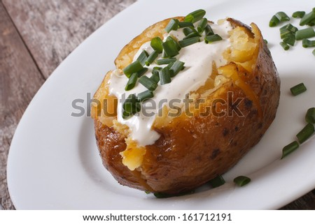 baked potato with sour cream and green onions - stock photo