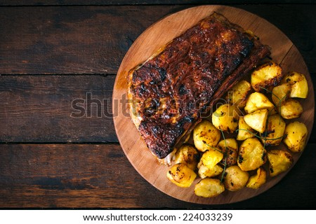 Baked potatoes and beef ribs in bbq sauce from above on wooden background.Blank space on the left side  - stock photo