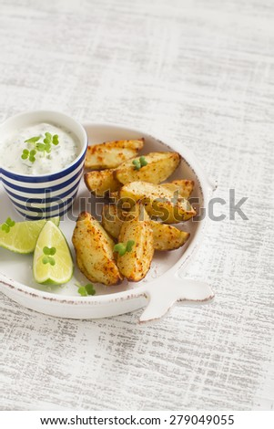 baked potatoes in a vintage plate on a light wooden surface - stock photo