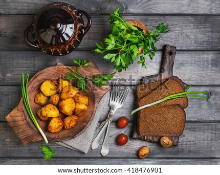 Baked potatoes roasted pieces, a ceramic pot saucepan of roasted pieces baked potatoes, rye bread, green onion, cherry tomatoes, silver fork, parsley, on a gray wooden rustic background, top view - stock photo